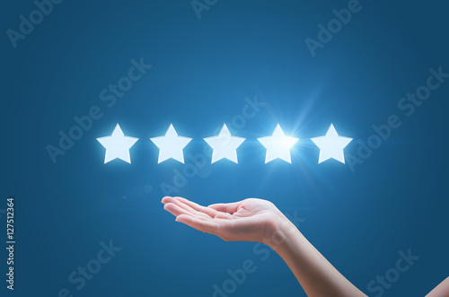 Cuadros en Lienzo Businesswoman hand holding five stars isolated on blue background