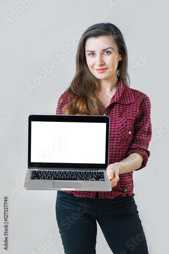 Valokuva  young girl holding a silver laptop and looking at the camera
