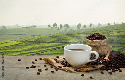 Poster Olive Hot Coffee cup with Coffee beans on the wooden table and the pla