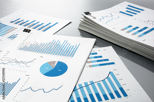 Prepareing report. Blue graphs and charts. Business reports and pile of documents on gray reflection background.