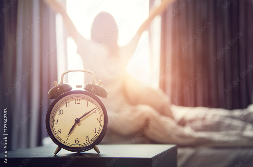 Fototapeta Closeup alarm clock having a good day with background happy woman stretching in bed after waking up, sunlight in morning.