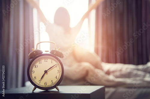 Fotografie, Obraz  Closeup alarm clock having a good day with background happy woman stretching in bed after waking up, sunlight in morning