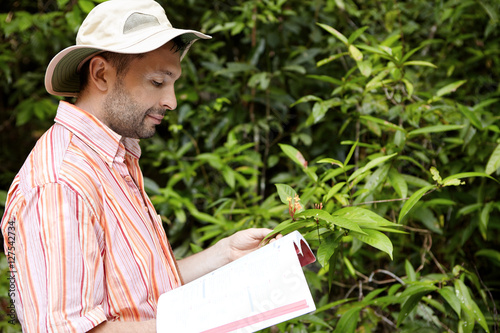 Valokuva  Handsome botanist with stubble wearing striped shirt holding manual or guide in one hand and green plant with flowers in another, studying its characteristics with happy and joyful look