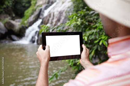 Fotografía  Rear view of biologist wearing panama hat taking picture of mountain waterfall in nature park using touch pad