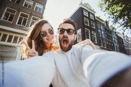 Poster Amsterdam Happy young couple in love takes selfie portrait near canals in Amsterdam, Netherlands.