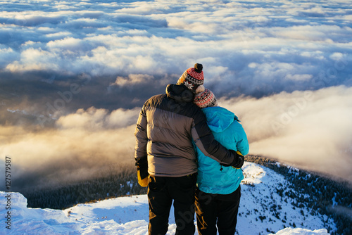 Photo  Loving couple stands on a top of the mountain and admire the inc