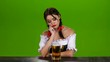 Girl in Bavarian costume sitting at the table with drinks beer. Green screen