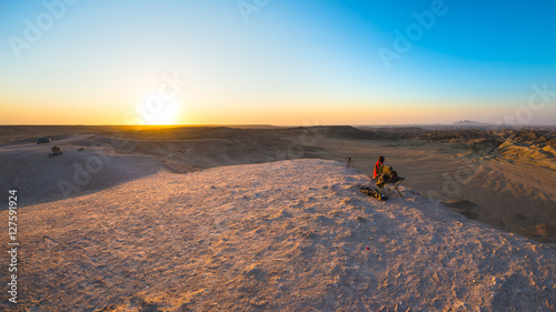 Papiers peints Route 66 Rear view of woman sitting on rocks and looking at expansive view over the scenic Namib desert at dusk time. Travel in the Namib Naukluft National Park, Namibia, Africa.