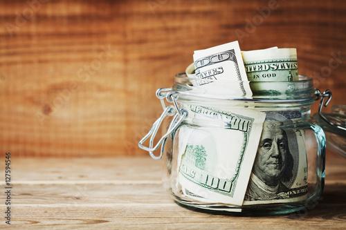 Papel de parede Dollar bills in glass jar on wooden background