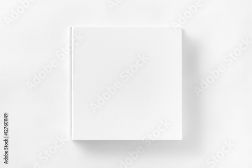 Mockup of closed blank square book at white textured paper