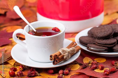 Photo Stands Coffee beans Tea with chocolate cookies on a background of autumn leaves