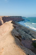 Rough coast line with towering cliffs and wild ocean in Angola