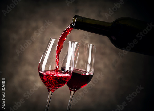 Foto op Aluminium Wijn Red wine pouring into glass from bottle