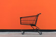 canvas print picture - Minimalism style, Shopping cart and orange wall.