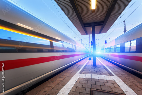 High speed passenger trains on railroad platform in motion at dusk Wallpaper Mural