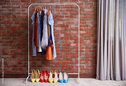 Hangers with different female clothes on brick wall