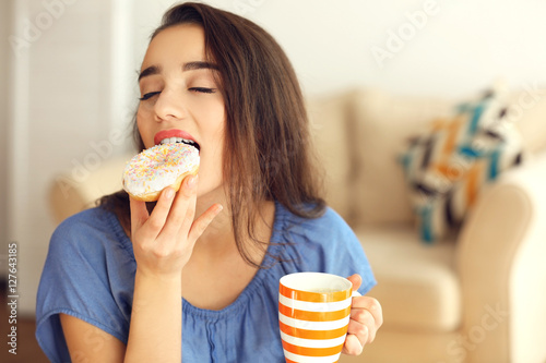 Photo  Beautiful young woman with tasty donut and cup of coffee on blurred background