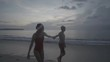 Christmas happy couple relaxing on the beach while walking on the sand in bikini and swimsuit. Woman and man wearing santa hat enjoying travel holidays during christmas time - video in slow motion