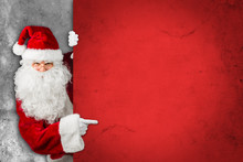 Santa Claus Hiding And Looking Through Behind Empty Red Concrete Billboard  Wall And Pointing With His Finger On It
