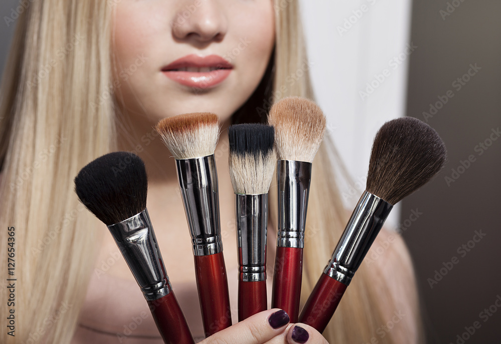 Poster  beautiful young blond woman and brush for makeup