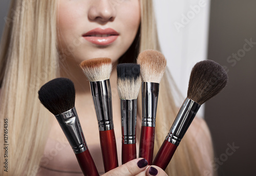 beautiful young blond woman and brush for makeup Plakat