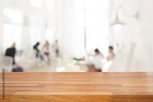 Láminas  Empty wooden table and blurred people in cafe background, produc