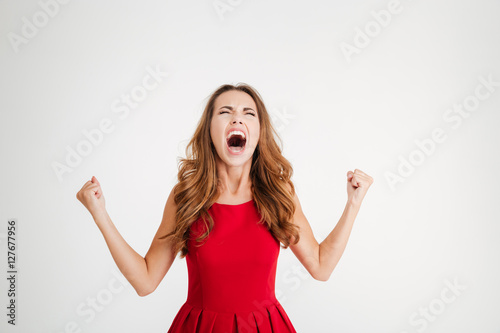 Fotografie, Obraz  Mad furious young woman with raised hands standing and screaming