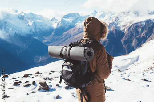 Tuinposter Wit Hiker in mountains in winter