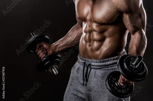 Powerful Body of Athlete Bodybuilder Posing with Dumbbells Plakat