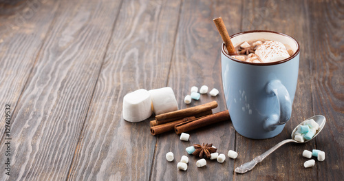 Foto op Plexiglas Chocolade Blue Cup of hot Chocolate drink with Marshmallows and cinnamon on dark wooden background. Winter time. Holiday concept