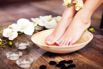 Fototapeta na wymiar Closeup photo of a female feet at spa salon on pedicure procedur