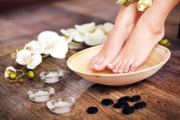 Obraz na płótnie Canvas Woman washing beautiful legs in bowl, on light background. Spa p