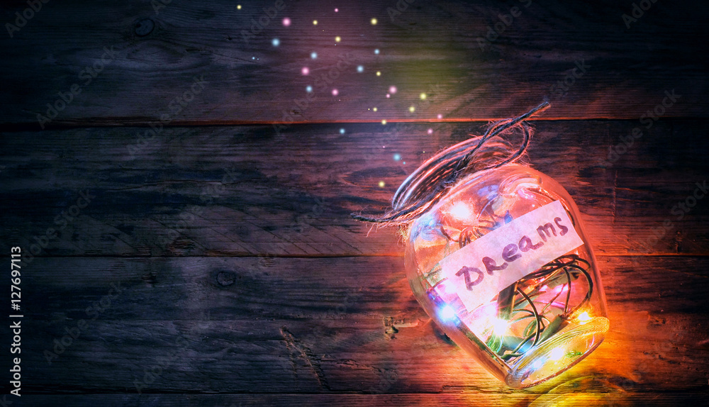 Fototapeta garlands of colored lights in glass jar with dreams