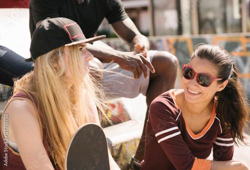 Two female friends chatting in city skatepark