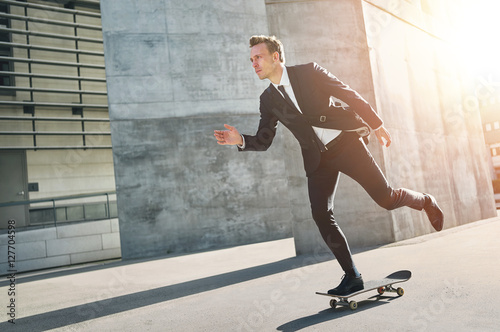 Fotografia  Extremal man wearing suits rides a skateboard