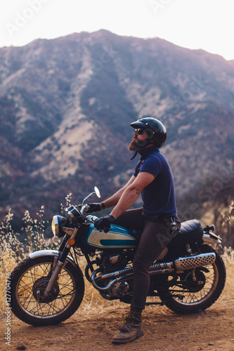 Man sitting on motorbike, looking at view, Sequoia National Park, California, US Poster