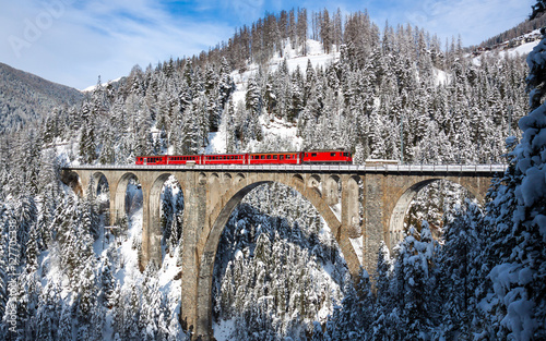 Train ride over bridge of snow covered mountains and trees Fotobehang