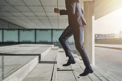 Photo  Man wearing suit runs up the stairs
