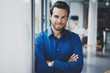 Portrait of successful confident hispanic businessman smiling and standing close from the window in modern office.Horizontal,blurred background.