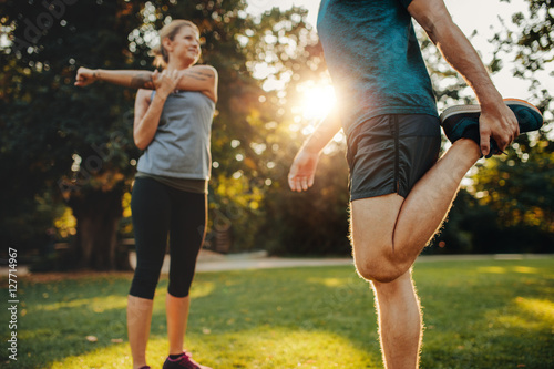 Fotografia Young man and woman stretching in the park