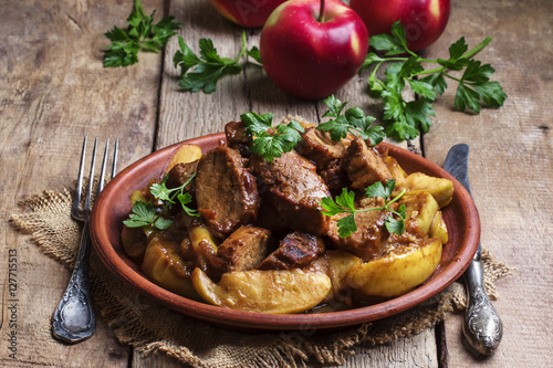 Foto op Aluminium Klaar gerecht Pork stew with apple sauce, vintage wooden background, selective