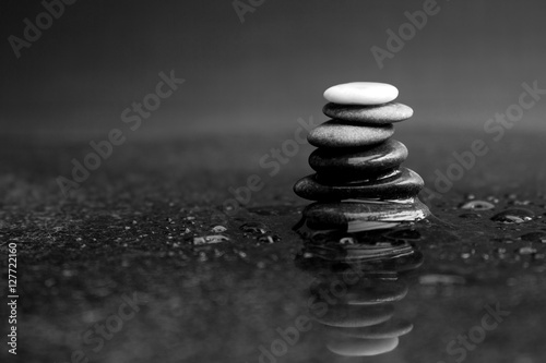 Fototapeta  Pebble stack in black and white with black pebbles and one white on the top lyin