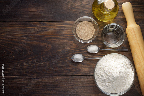 Fototapeta Baking wooden background with ingredients for pizza dough. obraz na płótnie