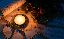 Christmas Decorations, Burning Candle And Sheet Music