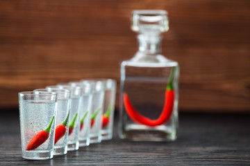 cold vodka with hot chili peppers , selectiv focus