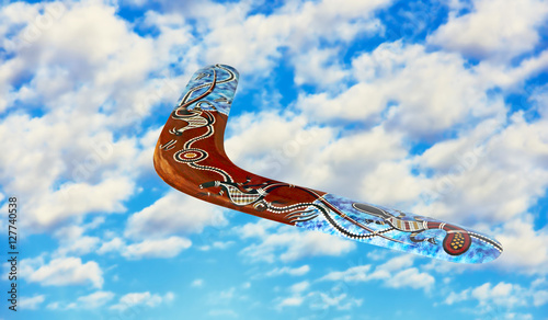 Photo Australian boomerang in flight against of blue sky and pure white clouds