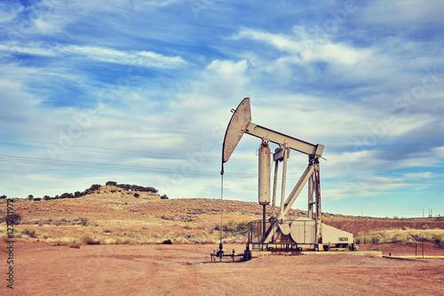 Fototapeta Retro toned picture of an oil pump, old industrial equipment on arid soil. obraz