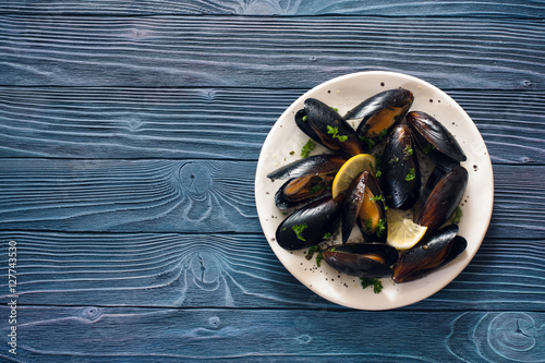 Valokuva  Mussels on white plate over blue wood background