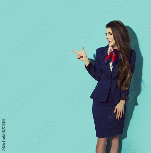 Charming Stewardess Dressed In dark Blue Uniform Pointing The Finger On blue Background. Young attractive beauty business woman smiling showing to the left.