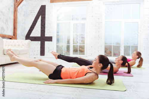 Three active women exercising hard in gym